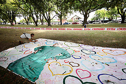 March 16, 2019 - Christchurch, New Zealand - Dylan Nunn writes on a sign at a memorial as a tribute to victims of the mosque attacks outside the Masjid Al Noor mosque. At least 49 people dead and more than 40 people injured following attacks on two mosques in  Christchurch. The national security threat level has been increased from low to high for the first time in New Zealand's history after this attack. (Credit Image: © Sanka Vidanagama/NurPhoto via ZUMA Press)