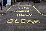 Keep Clear for fire access markings on cobbles outside residential buildings in a north London side street. Stencilled on the cobbled surface we see the yellow lettering outside a block of flats in central London. In order to keep the entrance clear of obstructions in times of perhaps fire or other events, when emergency services would need to get through the gates. Cobbled roads klike this are now rare, having been upgraded by local authorities and replaced by smoother and modern materials.