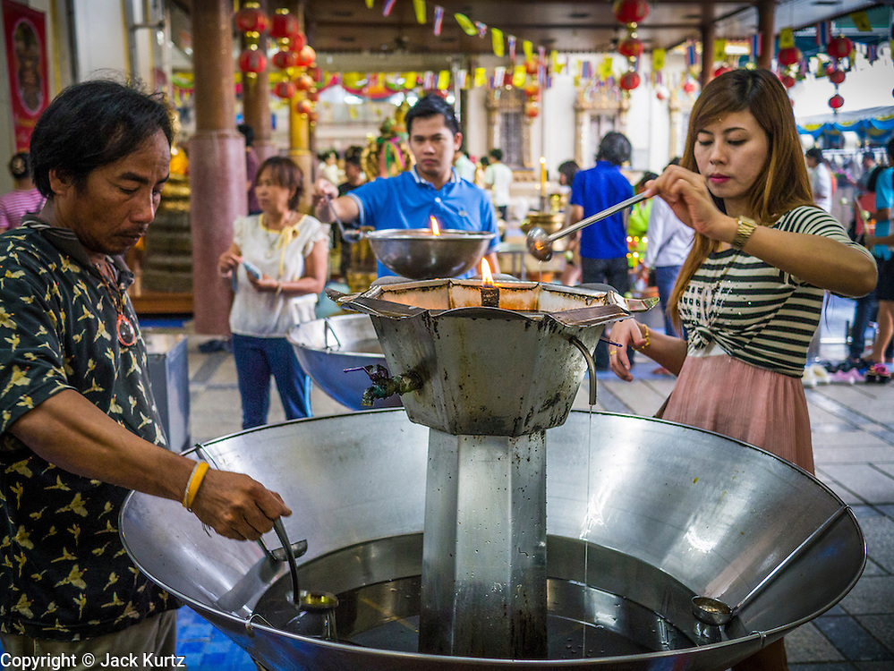 12 OCTOBER 2012 - RAI KHRING, NAKHON PATHOM, THAILAND:  Thai Buddhists pour oil into a lamp to make merit at Wat Rai Khring in Nakhon Pathom province. Wat Rai Khring was built in 1791, the Abbot at the time, Somdej Phra Phuttha Chan (Pook), named this temple after the district. When construction was completed, the Buddha image was brought from another temple and enshrined here. Later locals named the image ?Luang Pho Wat Rai Khing?. The Buddha image is of Chiang Saen style and is assumed to have been built by Lanna Thai and Lan Chang craftsmen.     PHOTO BY JACK KURTZ