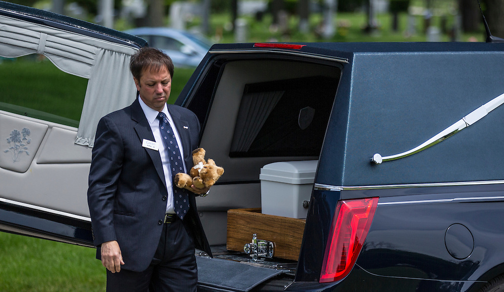 """Glueckert Funeral Home Funeral Director John Glueckert carries a teddy bear for an abandoned baby boy during a burial service at All Saints Cemetery in Des Plaines, Illinois, United States, June 19, 2015. More than a year after he was found dead in a plastic shopping bag on a Chicago sidewalk, the baby boy was buried by a non-profit group """"Rest in His Arms"""" after abandoned by his teenage mother, who is charged with murder.  REUTERS/Jim Young"""