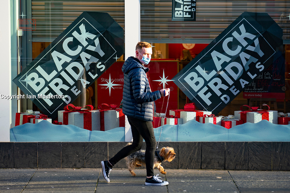 Glasgow, Scotland, UK. 25 November 2020. Glasgow city centre  very quiet during severe level 4 lockdown imposed by the Scottish Government.  Non essential businesses , bars, restaurants and shops are closed. Pictured;  Black Friday sales deals poster in closed shop on Buchanan Street. Credit.  Iain Masterton