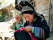 A 15 year old married Akha Nuquie ethnic minority woman sewing outside her home in Ban Pang Hok Kao village, Phongsaly Province, Lao PDR.  She is wearing the Akha Nuquie traditional costume made from hand woven cotton and dyed with indigo and decoarated with hand embroidery typical of the Akha Nuquie sub-group; the high headdress distinguishes her as a married women. One of the most ethnically diverse countries in Southeast Asia, Laos has 49 officially recognised ethnic groups although there are many more self-identified and sub groups. These groups are distinguished by their own customs, beliefs and rituals. Details down to the embroidery on a shirt, the colour of the trim and the type of skirt all help signify the wearer's ethnic and clan affiliations.