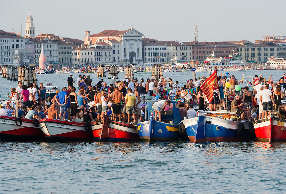 VENICE, ITALY - JULY 16: People starts to gather on boats of all sizes in St Mark's basin for the Redentore Celebrations on July 16, 2011 in Venice, Italy. Redentore is one of the most loved celebrations by Venetians which is a remembrance of the end of the 1577 plague. Highlights of the celebration include the pontoon bridge extending across the Giudecca Canal, gatherings on boats in the St Mark's basin and spectacular fireworks on display.