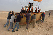 The ground crew of a hot air balloon operation push the basket towards more even ground after its landing on to wasteground in a West Bank village of the modern city of Luxor, Nile Valley, Egypt. These people are dependent of the tourism industry and therefore badly affected by the downturn. According to the country's Ministry of Tourism, European visitors to Egypt is down by up to 80% in 2016 from the suspension of flights after the downing of the Russian airliner in Oct 2015. Euro-tourism accounts for 27% of the total flow and in total, tourism accounts for 11.3% of Egypt's GDP so communities like this are suffering economically, as a result.