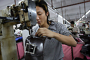30 March 2006 - Dongguan, Guangdong Province - Factory workers sew a bags on an assembly line in a handbad factory.