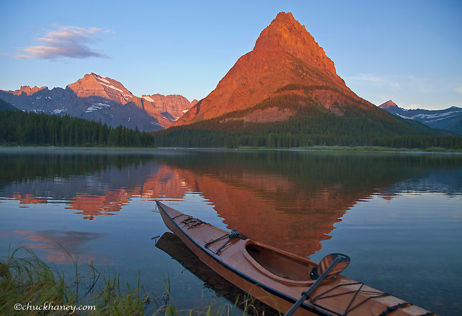Wooden kayak in Swiftcurrent Lake at sunrise in the Many Glacier Valley of Glacier National Park, Montana, USA