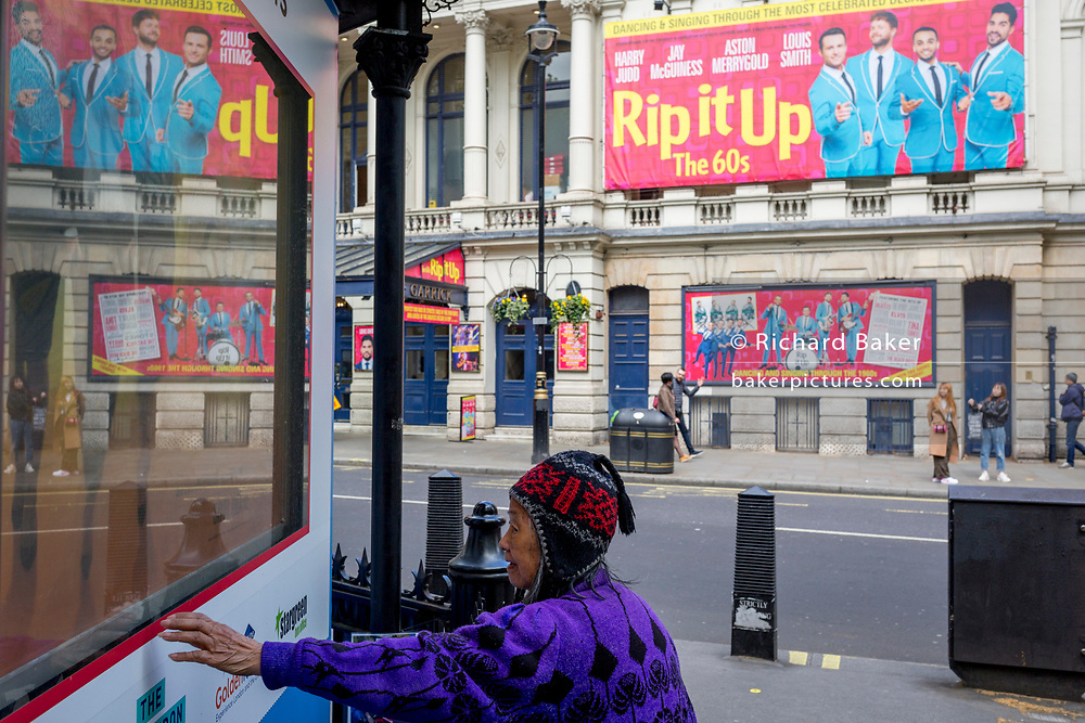 A Chinese lady touches a tourism booking office kiosk, opposite the Garrick Theatre currently showing the musical 'Rip It Up', on 29th April 2019, in London, England.