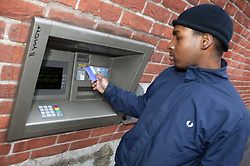 Single parent withdrawing cash from a hole in the wall cash machine,