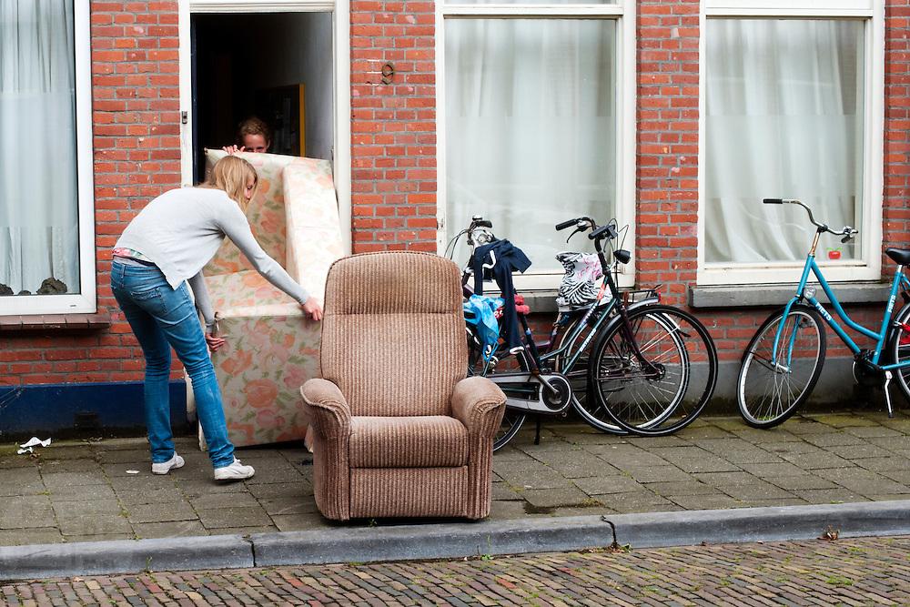 Twee studentes proberen een bank door de deur te krijgen.<br /> <br /> Two students are trying to put a couch as garbage out of their students home.