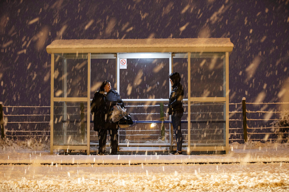 2 women waiting for bus in Stonehouse, South Lanarkshire.  Picture Robert Perry 8th Jan 2015<br /> <br /> Must credit photo to Robert Perry<br /> FEE PAYABLE FOR REPRO USE<br /> FEE PAYABLE FOR ALL INTERNET USE<br /> www.robertperry.co.uk<br /> NB -This image is not to be distributed without the prior consent of the copyright holder.<br /> in using this image you agree to abide by terms and conditions as stated in this caption.<br /> All monies payable to Robert Perry<br /> <br /> (PLEASE DO NOT REMOVE THIS CAPTION)<br /> This image is intended for Editorial use (e.g. news). Any commercial or promotional use requires additional clearance. <br /> Copyright 2014 All rights protected.<br /> first use only<br /> contact details<br /> Robert Perry     <br /> 07702 631 477<br /> robertperryphotos@gmail.com<br /> no internet usage without prior consent.         <br /> Robert Perry reserves the right to pursue unauthorised use of this image . If you violate my intellectual property you may be liable for  damages, loss of income, and profits you derive from the use of this image.
