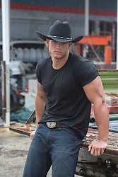 muscular, masculine cowboy at an auto garage in the rain