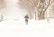 A man walks down a snow covered street during a blizzard in Rochester, New York.