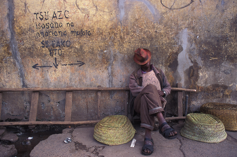 A market trader takes an afternoon nap on the pavement outside the main market of Antananarivo.