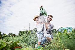 Mid adult man with his son watering plants in community garden, Bavaria, Germany