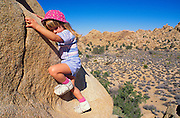 Child (age 3) climbing a granite boulder in Hidden Valley, Joshua Tree National Park, California
