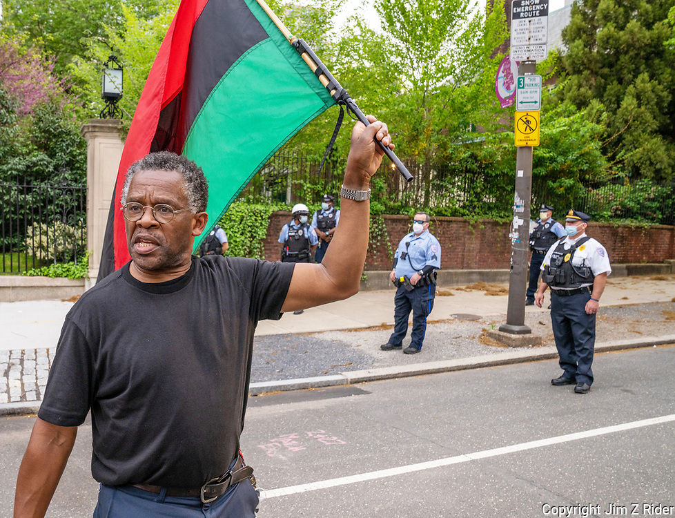 With Philadelphia police standing by, a protester waves a flag as he weaves through the crowd seated in front of the home of Penn's president.