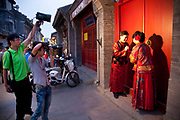 Photo shoot for a couple in traditional dress on Yandaixiejie Street (meaning Tobacco Pipe Lane) in Beijing, China. Located near to Houhai in downtown Beijing, Yandai Xiejie Street is a Hutong which attracts many tourists at day and night to it's souvenir shops and towards the bar area it leads to.