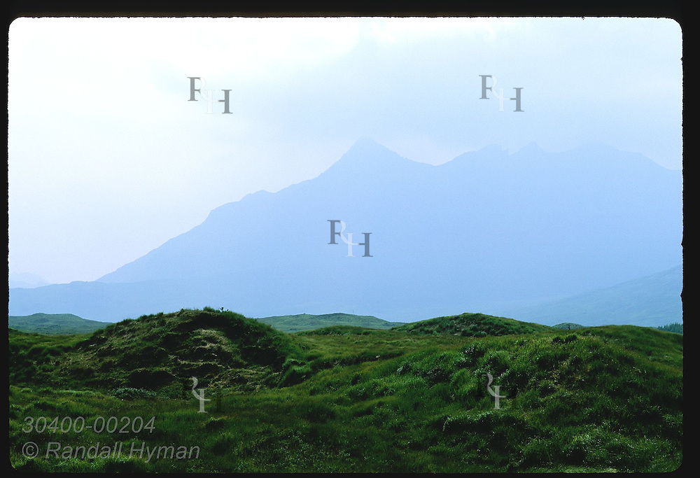 Misty mountains loom over grassy fields on a stormy July morning on the Isle of Skye. Scotland