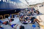 Refugees gather by a  ferry to escape direct sun during the day in Lesvos island, Greece on Aug 18th, 2015.
