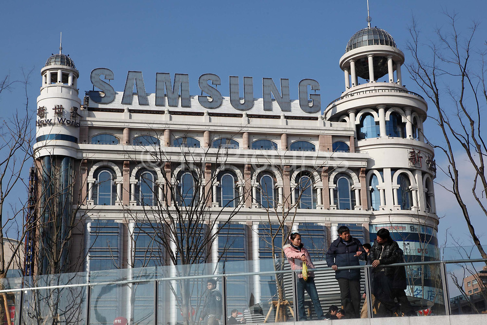 People relax in People's Park near the Nanjing Road pedestrian shopping street in downtown Shanghai, China on 28 January 2009.  A Samsung neon sign adorn the roof top of the New World Department Store in the back ground.