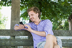 Mid adult man sitting on bench and using smart phone, smiling