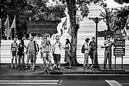 Tourist wait to cross the street at one end of Khao San Road (behind them is Wat Chana Songkhram Ratchaworamahawihan) in Bangkok, Thailand. (November 28, 2011)