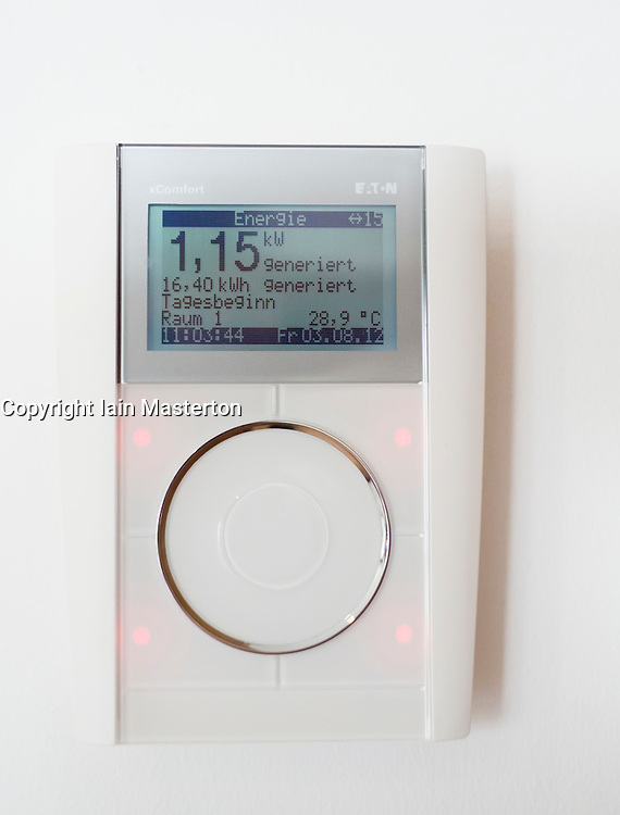 Wall mounted thermostat and energy display showing energy generated by solar panels in modern highly energy efficient family house  in Germany