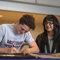 AJ Starkovich signs his letter of intent  to wrestle for Morningside College in Iowa while his mother Yvette Martinez looks on at Miyamura High School in Gallup, Wednesday.