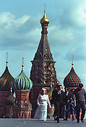 A Russian bride & groom walk through Red Square after having their pictures taken in front of St. Basil's Catherdral. It is traditional for wedding parties in Moscow to have their picture taken in Red Square.
