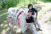 Asian American performers age 22 holding their festival dancing dragon. Dragon Festival Lake Phalen Park St Paul Minnesota USA
