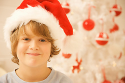 Close up of a boy wearing a red and white Christmas hat