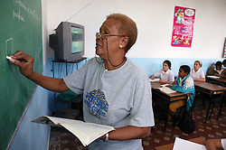 Black woman teacher writing on blackboard in classroom at Carlos J Finlay secondary school; Havana; Cuba,
