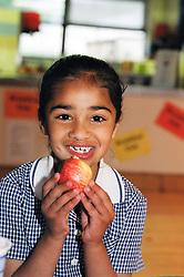 Schoolgirl eating an apple - fruit is given free to schoolchildren in Yorkshire; UK