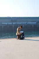 Dun Laoghaire Pier, Dublin, Ireland. Woman reading in the evening sunlight sitting on a mooring bollard.