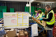 Male and female workers putting together veg boxes on a production line, Riverford Organics farm, Totnes, Devon, UK food industry