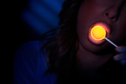 Young woman with her lips on a glowing tootsie pop.Black light