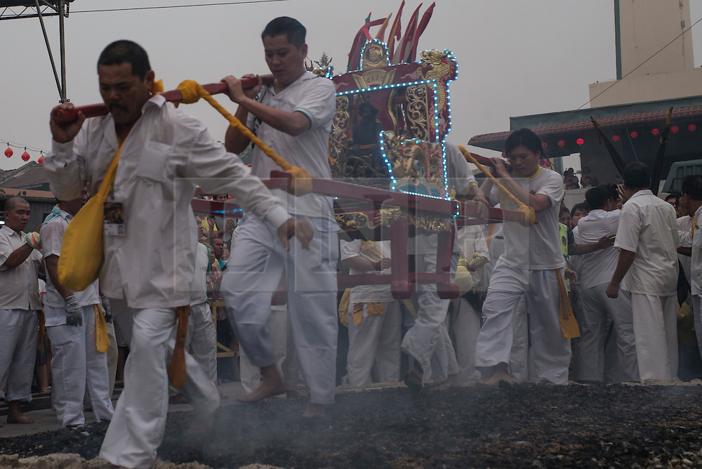 © Licensed to London News Pictures. 21/10/2015 Ipoh, Malaysia. Devotees carrying a Emperor God walk over a bed of hot embers to purify their souls during a fire-walking ceremony on the last day of the Nine Emperor Gods Festival at Tow Boh Keong temple in Ipoh, Malaysia, Wednesday, Oct. 21, 2015. The festival is a nine-day Taoist celebration to mark the birth of the Nine Emperor Gods from the first day to the ninth day of the ninth moon in Chinese Lunar Calender. The origin of the Nine Emperor Gods (stars of the Northern constellation) can be traced back to the Taoist worship of the Northern constellation during Qin and Han Dynasty and absorb this practice of worshipping the stars and began to deitify them as Gods. Photo credit : Sang Tan/LNP