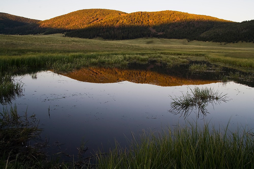 A hill - actually a resurgent dome formed by rising magma following the eruption and collapse that created the caldera - is reflected at sunset in a pond at the Valles Caldera National Preserve, New Mexico.