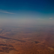 View through the window of a plane above the red desert of Central Australia.