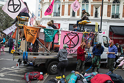 London, UK. 23rd August, 2021. Environmental activists from Extinction Rebellion stand around a vehicle used with lock-ons to block a road in the Covent Garden area during the first day of Impossible Rebellion protests. Extinction Rebellion are calling on the UK government to cease all new fossil fuel investment with immediate effect. Credit: Mark Kerrison/Alamy Live News