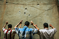 Ramadi, Iraq -- Iraqi males are forced at gunpoint to line up along an alley wall which bares scars of bullet holes while U.S. Marines search the men during a U.S. Marine patrol in Ramadi. The three young men were all traveling together in a single taxi cab. The patrol stopped the taxi to conduct a random inspection of the passengers and the contents of the vehicle in search of weapons or explosives. Nothing was found the the men were allowed to proceed without further detainment. -- Photo by Jack Gruber, USA TODAY