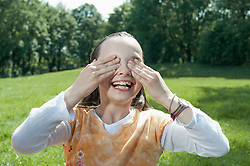 Girl wiping her face with water and smiling, Munich, Bavaria, Germany