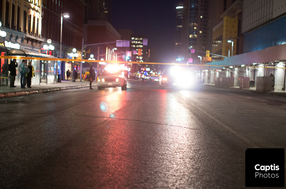 """Police investigate after a man was assaulted on Rideau St. between Sussex Dr. and Dalhousie St. A witness said the victim made """"racist comments"""" being assaulted by multiple attackers.<br /> Police say the man was unconscious when being transported to hospital and is in non-life threatening condition. March 31, 2015.<br /> Captis Photos / Brendan Montgomery"""