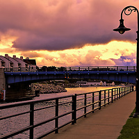 """""""Drawbridge at Charlevoix""""<br /> <br /> Sky drama, sunlight and clouds in the early morning along the walkway in Charlevoix Michigan heading towards the drawbridge."""