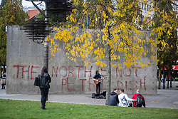 © Licensed to London News Pictures. 16/10/2020. Manchester, UK. A busker plays in front of anti lockdown graffiti in Piccadilly Gardens, Manchester. Manchester is on the verge of a Tier 3 lockdown. Photo credit: Kerry Elsworth/LNP