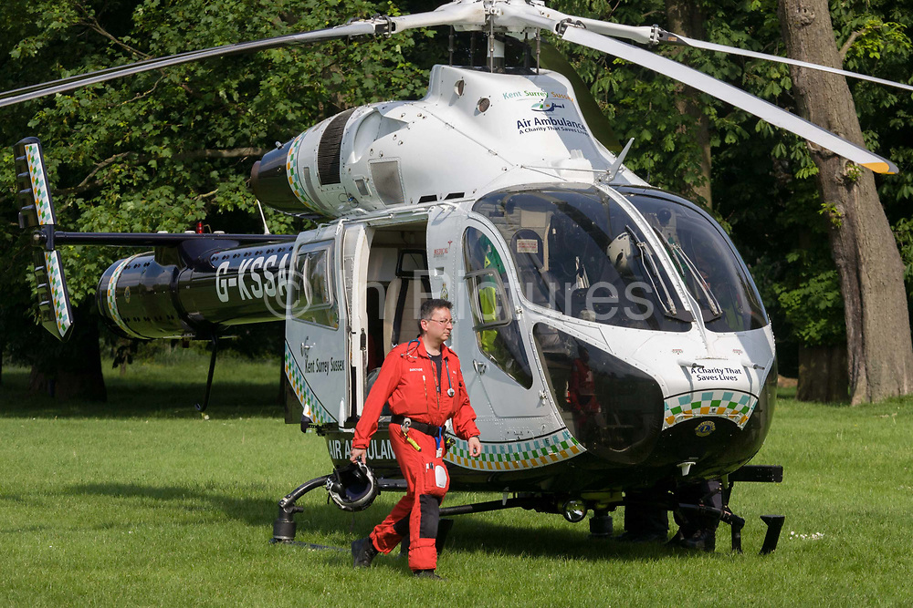 MD902 Explorer helicopter doctor crew from the Kent, Surrey & Sussex Air Ambulance Trust on the ground in Ruskin Park after emergency flight to Kings College Hospital in south London. A flight doctor walks around the nose of the aircraft before lifting off again for another emergency case. The Air Ambulance (KSSAAT) fly state of the art Helicopter Emergency Medical Service (HEMS) aircraft operating 365 days a year, out of their base at Marden in Kent and Redhill in Surrey. They're capable of delivering our crews anywhere in our region in under 20 minutes flying time, attending over 20,000 missions