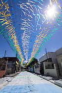 The scorching sun shines through Brazil national coloured ribbons in a street opposite the Arena da Amazonia, Manaus, Brazil, ahead of the England v Italy World Cup 2014 group match. Photo by Andrew Tobin/Tobinators Ltd