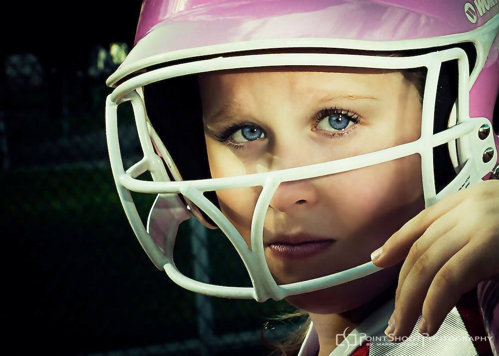Extreme Close up of female youth softball player wearing pink helmet. by PointShoot Photography, Stevensville, MD.