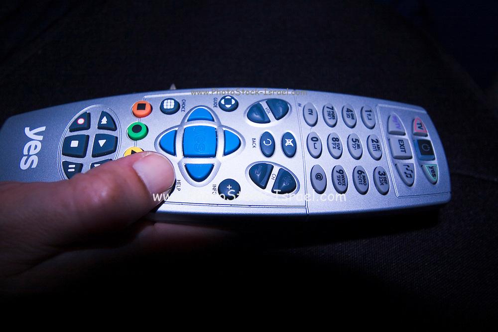 Man using a remote control, dark background