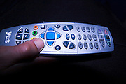 Man using a remote control, dark background